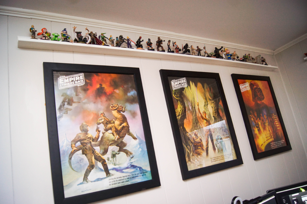 Star Wars posters on a wall with a shelf of miniatures above them.